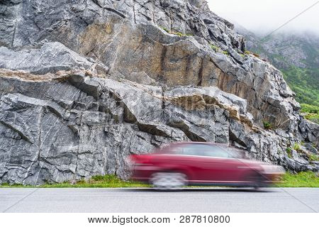 Blurry Car Driving Fast In Norway Mountains. Blurried Vehicle Riding Through Street In Nature.
