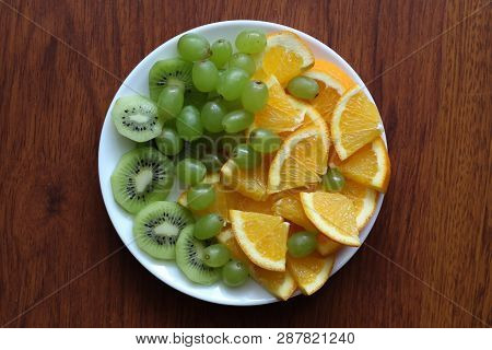 White Plate Filled With Various Fruits Stands On A Wooden Table