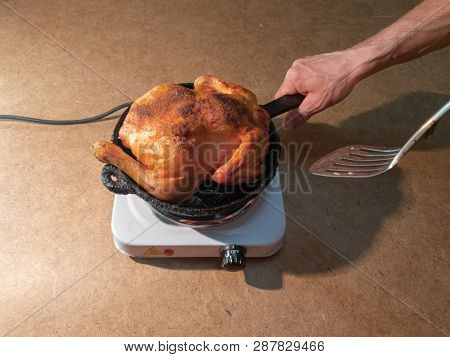 The Man Turns A Fried Chicken In A Pan On A Hotplate.cooking Fried Chicken