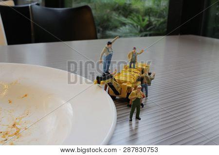 Miniature Figure Working On Empty Dish