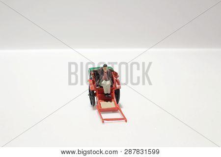 Miniature Statue And Red Vintage Oriental Rickshaw Cab