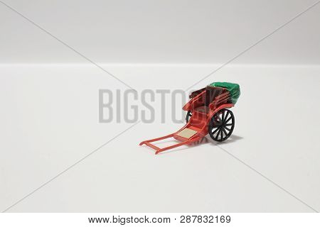 The Miniature Statue And Red Vintage Oriental Rickshaw Cab