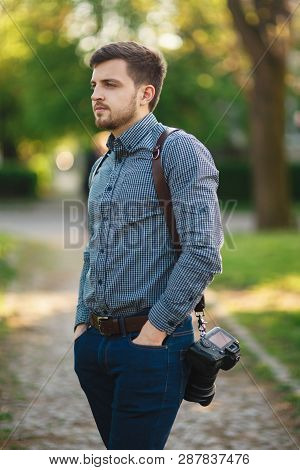 Portrait Of Handome Photographer Outside. Man Use Strap For Professional Camra. Expensive Lens