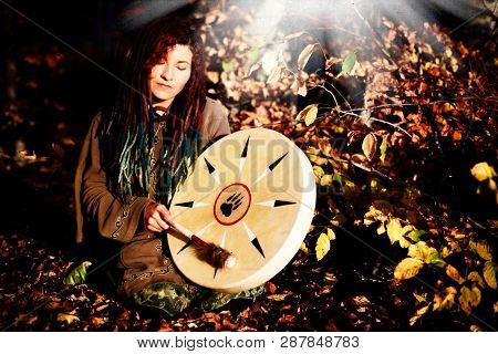 Beautiful Shamanic Girl Playing On Shaman Frame Drum On Background With Leaves And Flowers.