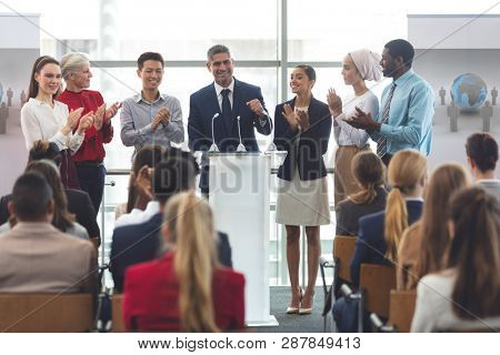 Front view of diverse group of business professionals standing on podium while speaking in front of business people at business seminar in office building