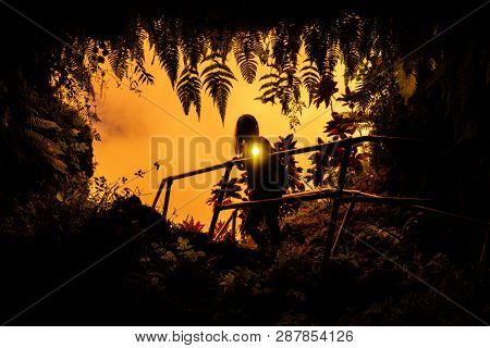 Woman stands near the entrance to the Lava Tube surrounded by lush tropical vegetation and flashes with the light of torch right into the camera. Maui, Hawaii
