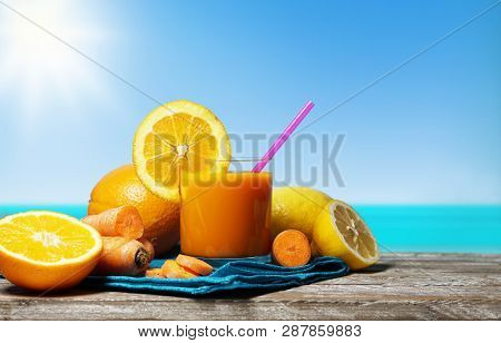 Carrot, orange and lemon juice. Healthy and refreshing fruity summer drink front view on a wooden table with blue sea and sky on background in a beautiful hot summer day. poster