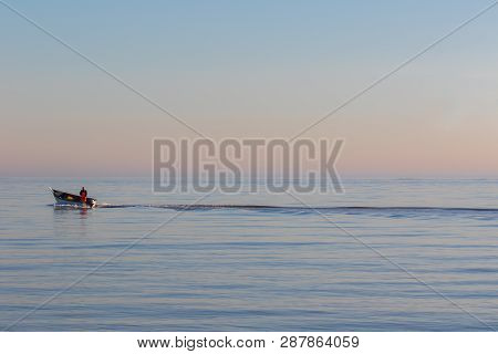 Solitude. Alone At Sea. Small Business Fishing Boat On The Ocean. Lone Fisherman On A Voyage Of Disc