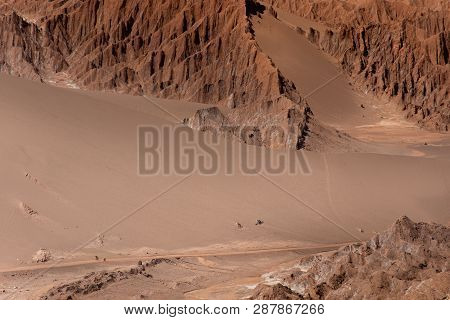 Two Mountainbikers Ride Their Bikes On A Road Of Sand Through The Desert Surrounded By Mountain Ridg