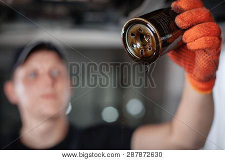 Replacing The Oil Filter. Specialist Auto Mechanic In The Car Service Repairs The Car..