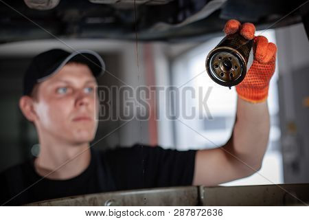 Specialist Auto Mechanic In The Car Service Repairs The Car. Replacing The Oil Filter.