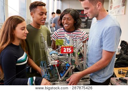 University Students Carrying Machine In Science Robotics Or Engineering Class