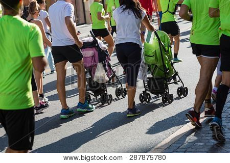 Parents With Pushchairs For Children In A City Marathon Race Event.