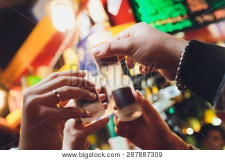 Male Hands Cheer With Glasses Of Shot Or Liqueur. Friends Drink Shot Or Liqueur And Cheers. Male Han