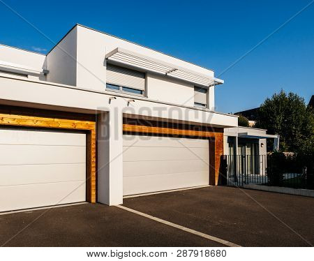 Modern House Architecture Style With Large Garage Automated Door Entrance - Clear Blue Sky