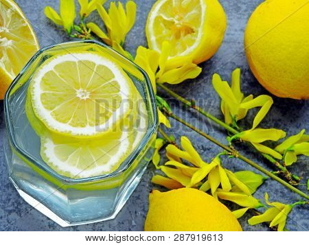 Detox Water With Lemon Juice. Lemon Water. Yellow Flowers On The Branches. Water With Lemon Wedges.