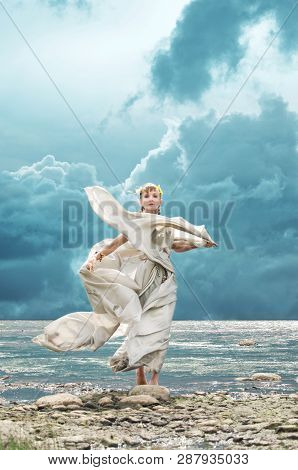 Woman In The Costume Of A Nymph Standing On The Beach In The Wind