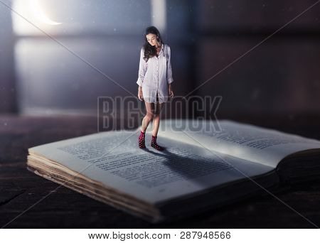 Good night concept with shrinked young woman reading book. Miniature unreal dreamy scene with moonlight