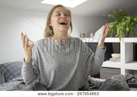 Sick Young Fair-haired Caucasian Woman In Grey Homewear Covered With Grey Blanket Sitting In Lotus P