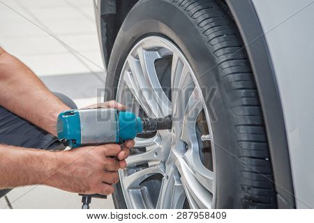 Car Repair: Wheel Replacement Closeup. Mechanic Screwing Or Unscrewing Car Wheel At Car Service Gara