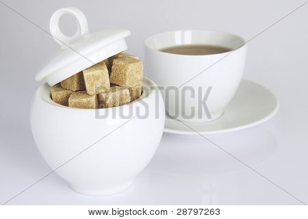 white sugar-bowl with brown sugarcubes and a cup of tea