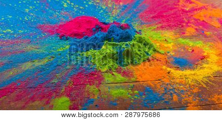 Abstract colorful Happy Holi background. Color vibrant powder on wood. Dust colored splash texture. Flat lay holi paint decoration
