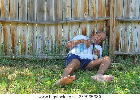 Alcoholic Male Homeowner Drunk In His Backyard Hiding From His Wife.