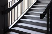 Empty Modern Concrete Staircase and black steel handrail with natural light, staircase in modern building - Dark Tone poster