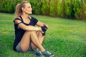 Female exercising outdoors, pretty blond woman relaxing after a good workout, listening music and meditating, sportive active lifestyle, wellbeing and healthy life of a young people