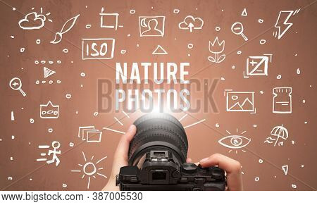 Hand taking picture with digital camera and NATURE PHOTOS inscription, camera settings concept