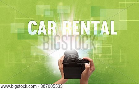 Close-up of a hand holding digital camera with CAR RENTAL inscription, traveling concept