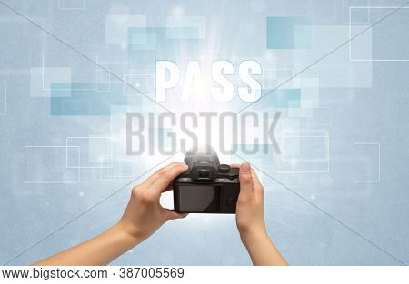 Close-up of a hand holding digital camera with PASS inscription, traveling concept