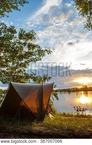 Fishing Adventures, Carp Fishing. Angler, At Sunset, Is Fishing With Carpfishing Technique. Camping