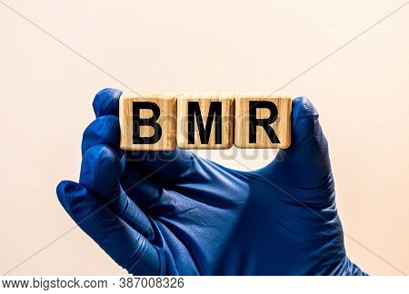 The Word Bmr Which Is Made From Wooden Cubes. Hands In A Blue Glove. Isolated On White Background.