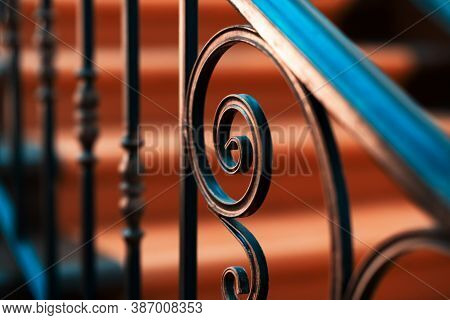 Forged Metal Railings In Black Color Inside The Room. The Background Is Blurred.