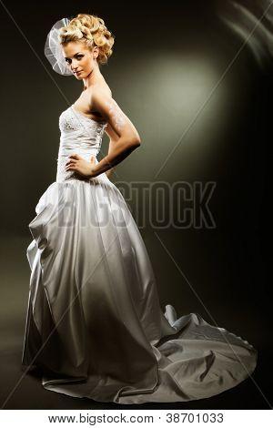 beautiful girl wearing luxurious wedding dress over studio background