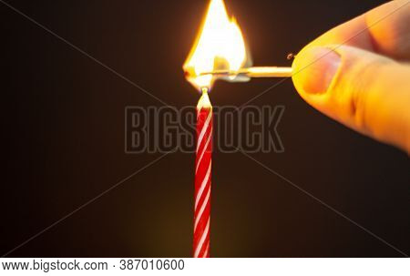 Lights Candle. Birthday Candle On Black Background. Red Birthday Candle