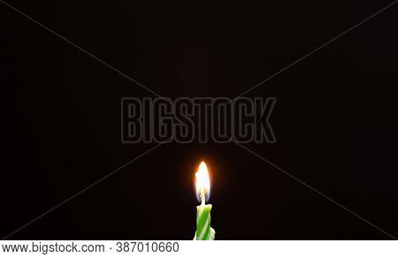 Birthday Candle On Black Background. Burning Birthday Candle On Black Texture. Green Birthday Candle