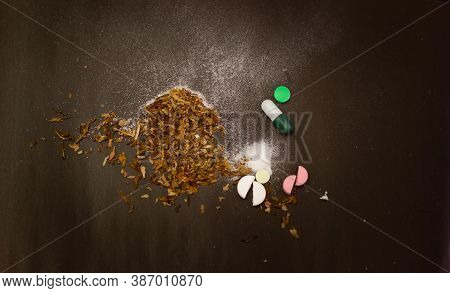 White Powder And Pills On A Black Background. Tobacco On The Black Table. Pills, Powder, Tobacco On