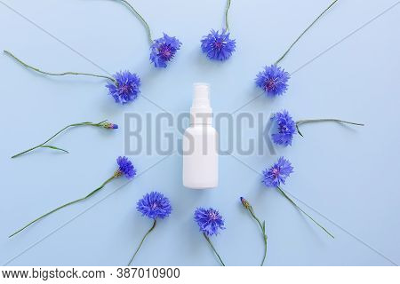 Mockup Of Unbranded White Plastic Spray Bottle And Floral Frame Of Blue Lowers On A Pastel Blue Back