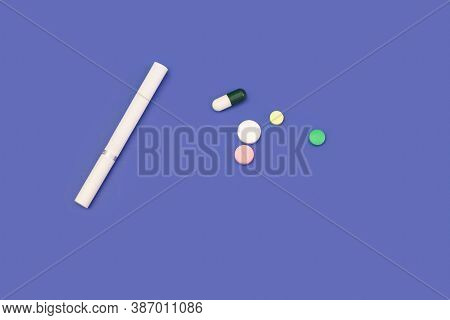 Cigarette And Pills On Blue Background. Cigarette On Blue Table. Pills On Blue Background. Cigarette
