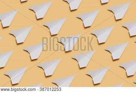 Set Of Paper Planes On Yellow Paper. Lots Of White Paper Planes On A Yellow Background