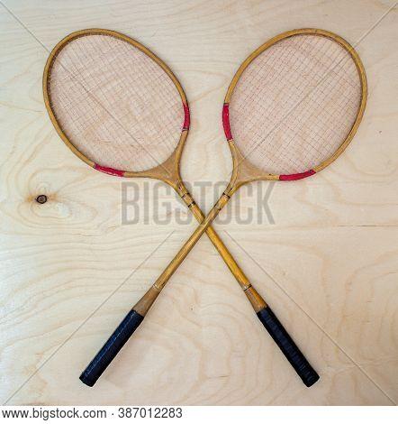 Vintage Badminton Racket On A Wooden Background. Badminton Racket On Plywood. Racket And Shuttlecock