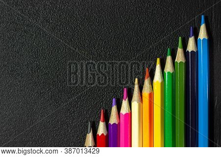 Set Of Colored Pencils On A Black Background. Colored Pencils On A Chalk Board. Black Texture With C
