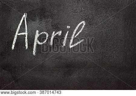 Month Written In White Chalk On A Chalkboard. The Month Depicted On The Chalkboard Is April