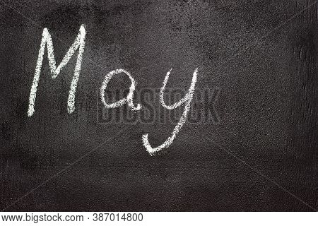 Month Written In White Chalk On A Chalkboard. The Month Depicted On The Chalkboard Is May