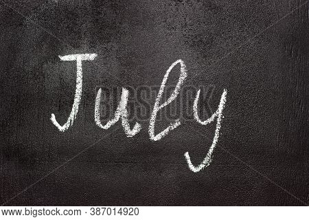 Month Written In White Chalk On A Chalkboard. The Month Depicted On The Chalkboard Is July