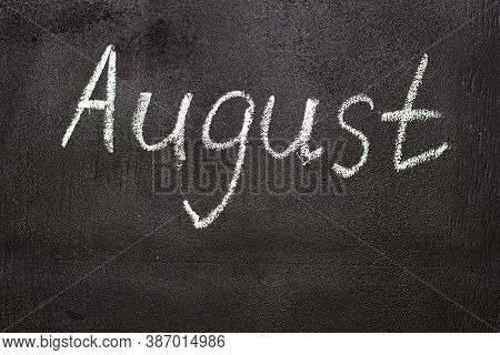 Month Written In White Chalk On A Chalkboard. The Month Depicted On The Chalkboard Is August