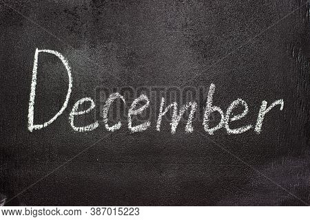 Month Written In White Chalk On A Chalkboard. The Month Depicted On The Chalkboard Is December
