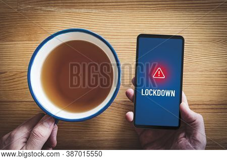 Lockdown Notification Concept On Smart Phone. Person Read Alert During Breakfast On Smartphone About